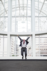 A businessman jumping for joy in front of a large window in a convention centre lobby.の写真素材 [FYI02262939]