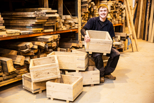 Man sitting in a warehouse in front of shelves with wooden planks, holding wooden crate, smiling atの写真素材 [FYI02262944]
