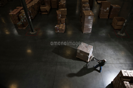 Warehouse worker using a manual pallet jack to move some products in a distribution warehouse.の写真素材 [FYI02262950]