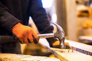 Close up of person wearing work gloves holding, hammer, removing rusty nails from recycled wooden plの写真素材 [FYI02262954]