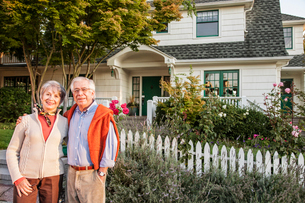 Hispanic senior couple in front of their remodelled older style home.の写真素材 [FYI02262956]