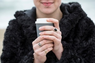 Close up of young woman wearing black furry jacket holding paper cup with hot drink.の写真素材 [FYI02262960]