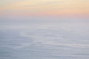 The open ocean, water surface calm and grey and the glow of the sun at dawn on the horizon.の写真素材 [FYI02262968]