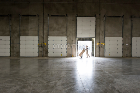 A warehouse worker with a hand truck walking past an open loading dock door in a large distributionの写真素材 [FYI02262974]