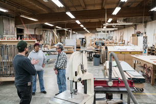 A group of mixed race carpenters discussing a project at a work station in a large woodworking shop.の写真素材 [FYI02262976]