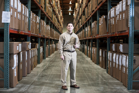 A Hispanic male warehouse worker standing next to racks of boxed products in a distribution warehousの写真素材 [FYI02262993]