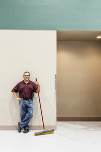 An Hispanic workman standing in a large interior space with a broom.の写真素材 [FYI02262994]