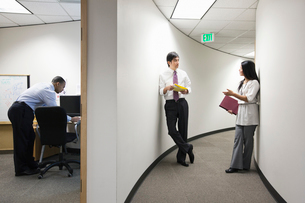 Two Asian businesspeople talking in a hallway near a black businessman working alone in his office.の写真素材 [FYI02263004]