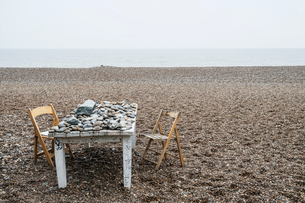 Old rickety white wooden label covered in pebbles and two folding chairs on a shingle beach by the oの写真素材 [FYI02263006]