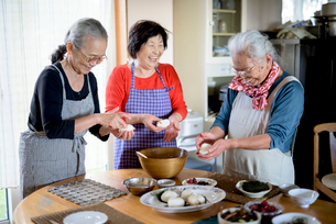 Three older women standing round a table in a kitchen, making sushi.の写真素材 [FYI02263009]
