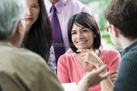 Hispanic businesswoman listening to someone talk during a business meeting with other team members.の写真素材 [FYI02263013]