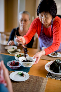 Woman wearing apron standing at kitchen table, holding bowl, serving food with chopsticks.の写真素材 [FYI02263014]