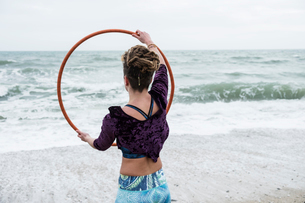 Young woman with brown hair and dreadlocks standing on a sandy beach by the ocean, balancing hula hoの写真素材 [FYI02263018]