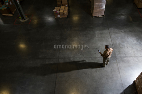 A storeroom manager seen from above in a darkened warehouse, looking at his phone.の写真素材 [FYI02263021]