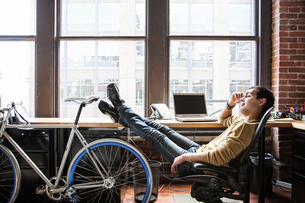 Hispanic man at his office workstation with a bicycle.の写真素材 [FYI02263030]