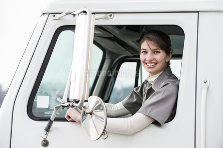 Portrait of a Caucasian female truck driver in the window of her truck at a distribution warehouse.の写真素材 [FYI02263037]