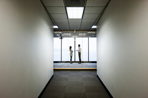 Male and female business people talking and standing in front of a window at the end of a long hallwの写真素材 [FYI02263039]