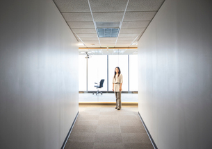 An Asian businesswoman standing alone in her office  space.の写真素材 [FYI02263042]