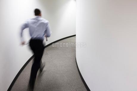 A blur of a businessman running in an office hallway.の写真素材 [FYI02263044]