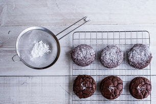 A tray of cooling chocolate brownies, and a sieve with icing sugar for decoration.の写真素材 [FYI02263046]