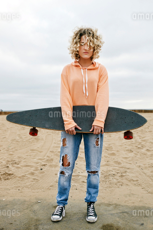 Young woman with curly blond hair wearing pink hoodie and ripped jeans standing on sandy beach, holdの写真素材 [FYI02263052]