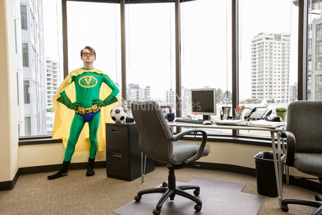 A Caucasian man office super hero stands at his office window pondering his next move.の写真素材 [FYI02263059]