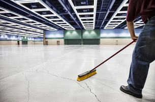 A low view closeup of a man sweeping the floor of a convention centre arena.の写真素材 [FYI02263061]