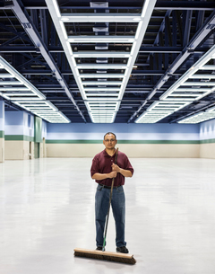 An Hispanic man standing with a broom in a large convention cener space.の写真素材 [FYI02263062]