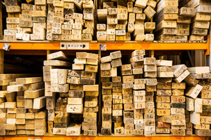 Large selection of wooden planks stacked on shelves in a warehouse.の写真素材 [FYI02263063]