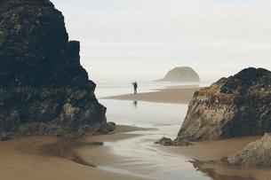 Man taking photos on beach at low tide, Arcadia Beach State Park, Oregonの写真素材 [FYI02263073]