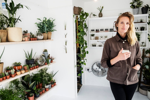 Female owner of plant shop smiling at camera, a selection of plants on wooden shelves.の写真素材 [FYI02263075]