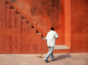 Rear view of man sweeping floor in front of red building with staircase.の写真素材 [FYI02263079]
