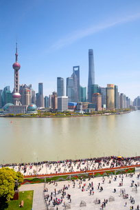 City skyline with tall skyscrapers across river, crowds on promenade.の写真素材 [FYI02263088]