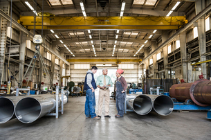 Mixed race team of workers and management people in a large sheet metal factoryの写真素材 [FYI02263093]