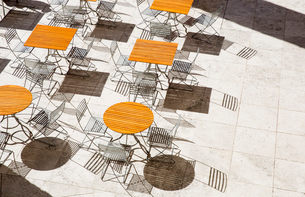 High angle view of wooden tables and metal folding chairs casting shadows onto brown paving.の写真素材 [FYI02263096]