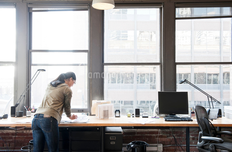 Asian woman working at her office workstation in a creative office.の写真素材 [FYI02263098]