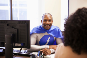 A black businessman office super hero in a meeting with an office team member.の写真素材 [FYI02263101]