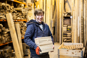 Smiling blond woman wearing work gloves standing in a workshop, holding stack of wood, looking at caの写真素材 [FYI02263109]