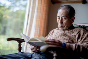 Elderly man sitting in rocking chair by a window, reading book.の写真素材 [FYI02263111]