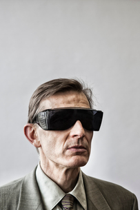 Studio portrait of Caucasian man actor wearing large sunglasses or protective eyeglasses with darkenの写真素材 [FYI02263115]