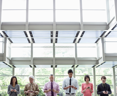 A mixed race group of male and female business people standing in the lobby area of a convention cenの写真素材 [FYI02263116]
