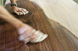 Caucasian man factory worker applying finish to a recycled wood table top in a woodworking factoryの写真素材 [FYI02263127]