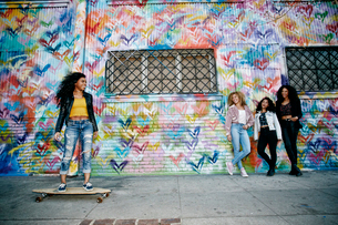 Four young women with curly hair standing in front of shutter covered in colourful graffiti, one ridの写真素材 [FYI02263133]