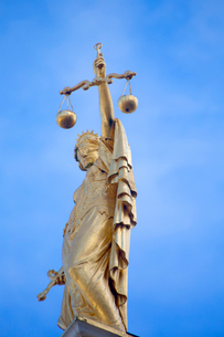 Low angle view of golden statue of Justice, blindfolded female holding aloft weighing scales.の写真素材 [FYI02263136]