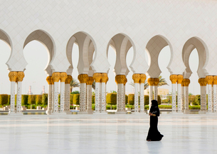 Woman walking past colonnade of mosque with white washed and golden columns.の写真素材 [FYI02263140]