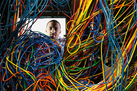 A black male technician working on a tangled mess of CAT 5 cables in a server room.の写真素材 [FYI02263141]