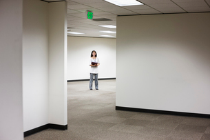 An Asian businesswoman standing alone in her office  space.の写真素材 [FYI02263142]