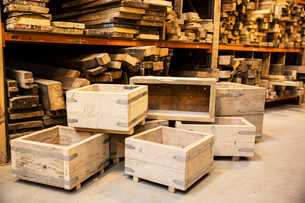 Shelves with wooden planks and a stack of wooden crates in a warehouse.の写真素材 [FYI02263145]