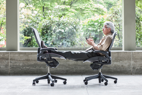 An Asian businessman checking his phone, sitting in a chair and resting his feet in another chair.の写真素材 [FYI02263147]