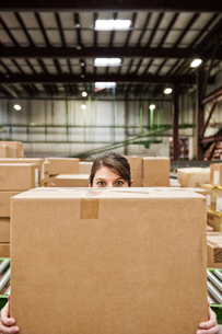 A Caucasian female warehouse worker behind a cardboard box in a distribution warehouse.の写真素材 [FYI02263157]